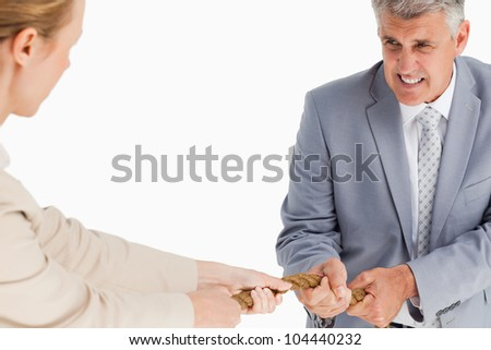 Businessman pulling a rope against white background - stock photo