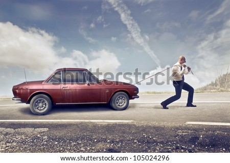 Businessman pulling an old car - stock photo
