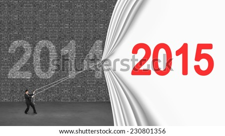 businessman pulling down 2015 curtain covering old 2014 brick wall on gray concrete floor - stock photo