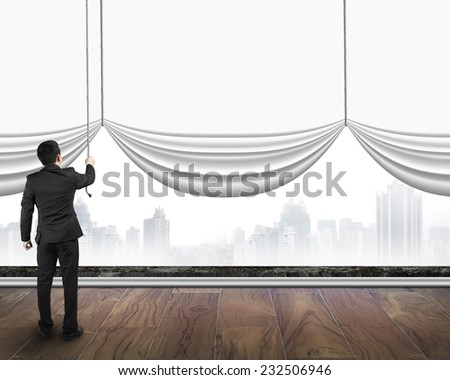 businessman pulling open blank white curtain covered gray cityscape background on wooden floor - stock photo