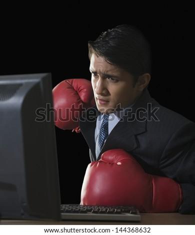 Businessman punching a desktop pc - stock photo