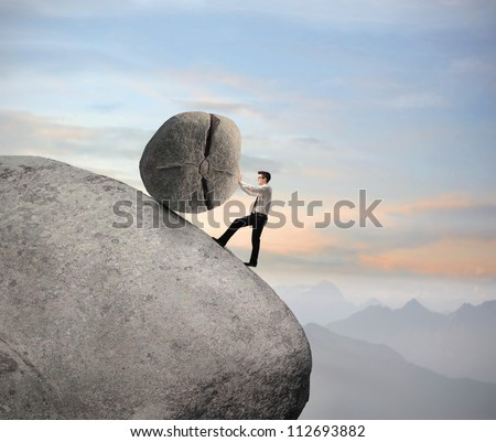 Businessman pushing a boulder on a rock - stock photo