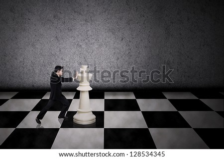 Businessman pushing a chess piece on grey background