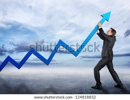 Businessman pushing a graphic arrow up - stock photo