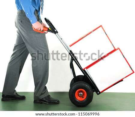 Businessman pushing a manual trolley. Two white blank boxes. - stock photo
