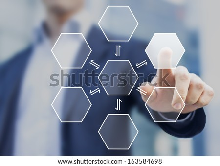 Businessman pushing a virtual hexagonal button with office buildings in background