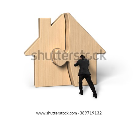Businessman pushing assembling wooden house puzzles, isolated on white background. - stock photo