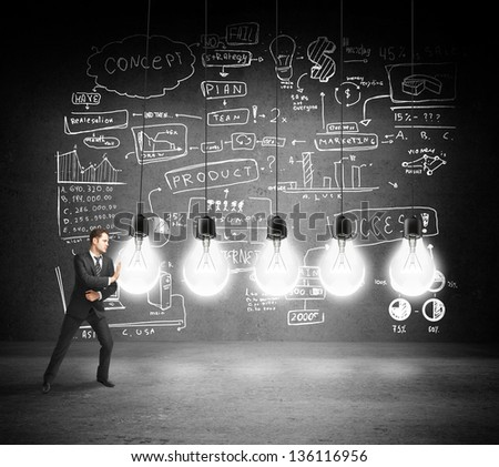 businessman pushing bulbs with drawing concept on concrete wall - stock photo