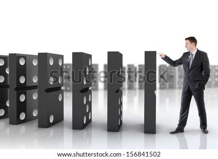 Businessman pushing dominoes - stock photo