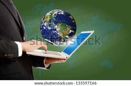 Businessman pushing on laptop keyboard for Business Concept with World Map Globe. Earth image provided by Nasa. - stock photo