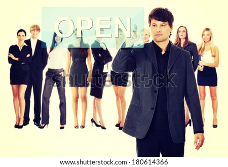 Businessman pushing OPEN on a touch screen interface. Business team at background - stock photo