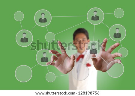 Businessman pushing people Social Network on the green data background - stock photo
