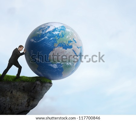 Businessman pushing planet Earth off the cliff. Elements of this image furnished by NASA