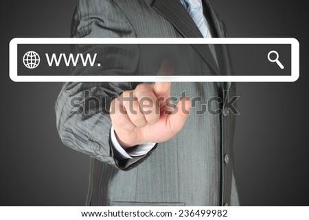 Businessman pushing virtual search bar on black background, internet concept   - stock photo