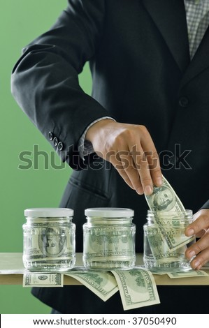 businessman put dollars in glass jar - stock photo