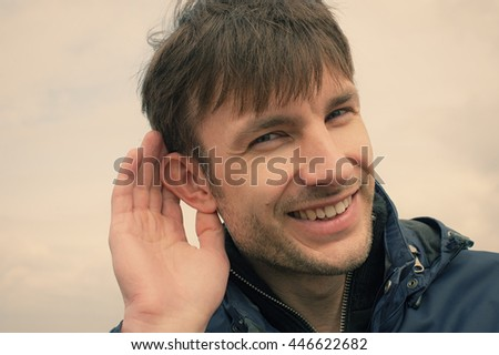 businessman put his hand to his ear listening