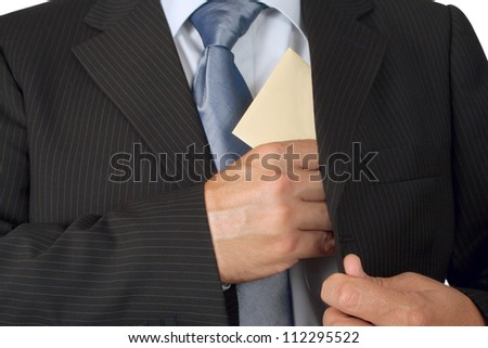 Businessman putting an envelope in his jacket pocket - concept of bribe - stock photo