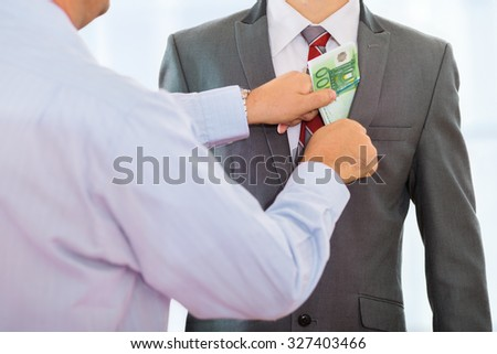 Businessman putting bribe money into another businessman's suit pocket - stock photo