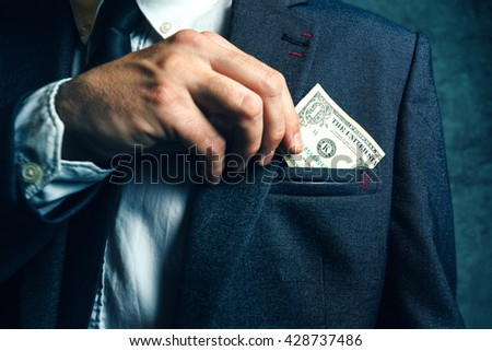 Businessman putting dollar banknotes money in his suit pocket, elegant businessperson with cash. - stock photo