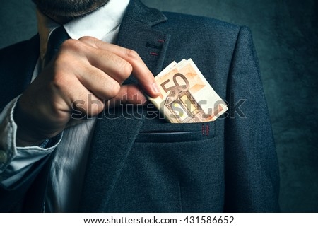 Businessman putting euro banknotes money in his suit pocket, elegant businessperson with cash. - stock photo