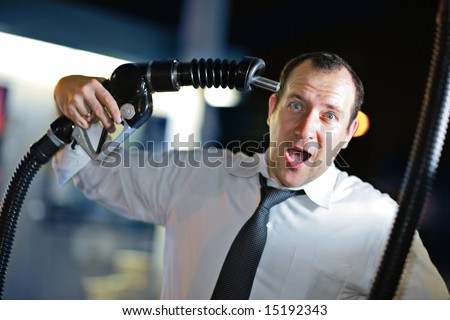 Businessman putting gas nozzle to his head, screaming. - stock photo