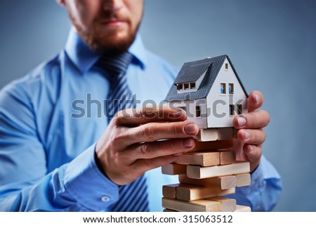 Businessman putting house model on top of tower from small wooden blocks - stock photo