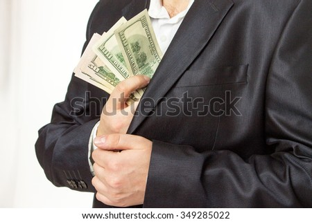Businessman putting money in suit jacket pocket