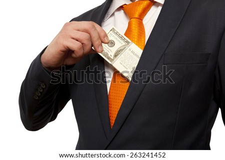 Businessman putting money in suit jacket pocket, concept for corruption, bribing