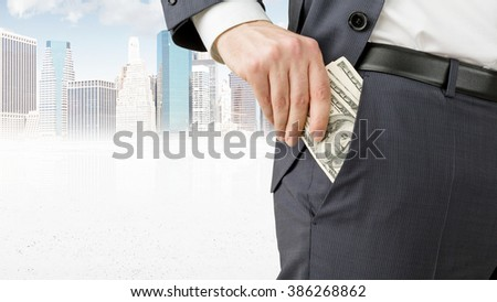 Businessman putting one hundred dollar banknotes into the pocket. Only trousers seen. New York at background. Concept of winning a fortune. - stock photo