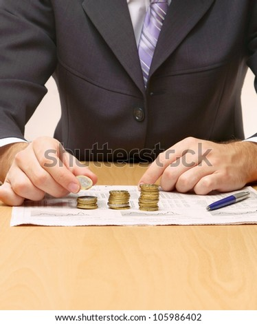 Businessman putting the coins in columns - stock photo