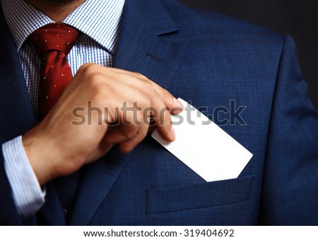 Businessman putting visit card in the pocket.