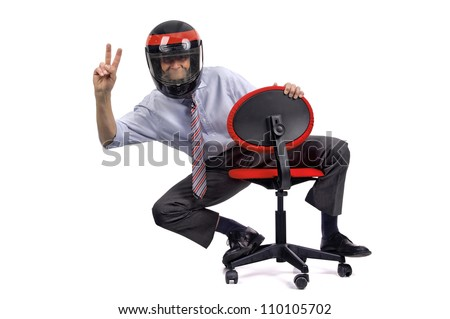 Businessman racing in a chair with helmet - stock photo