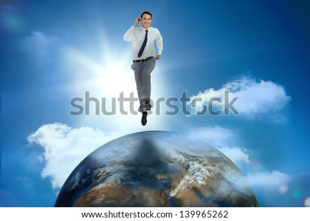 Businessman racing on top of the world in sunny blue sky