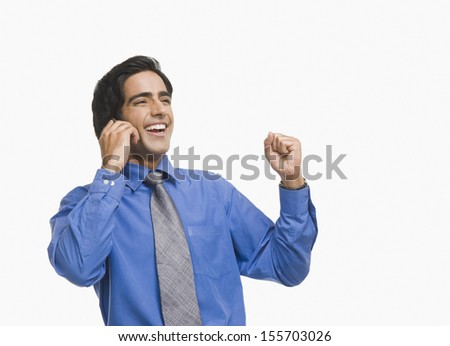 Businessman raising fist while talking on mobile phone - stock photo