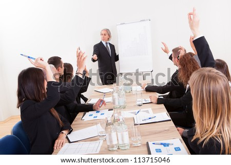 Businessman Raising His Hand Up At A Conference - stock photo