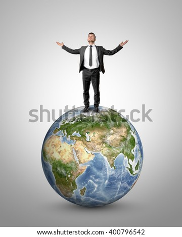 Businessman raising his hands to heaven standing on Earth globe. Elements of this image are furnished by NASA - stock photo