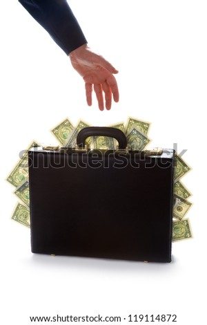businessman reaching for a briefcase bursting with american dollars