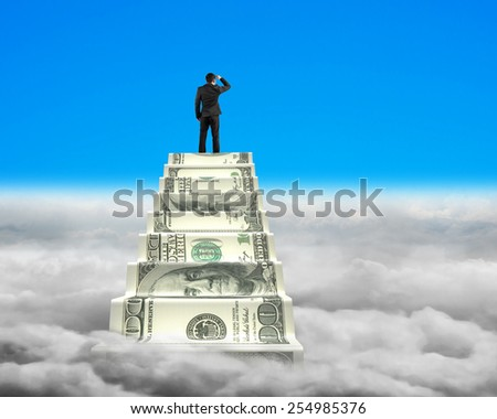 Businessman reaching the top of money stairs looking around blue sky with cloudscape background - stock photo
