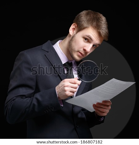 Businessman reading a document through a magnifying glass.