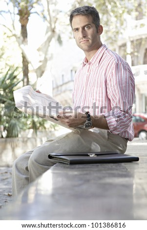 Businessman reading a financial newspaper in the city, outdoors. - stock photo