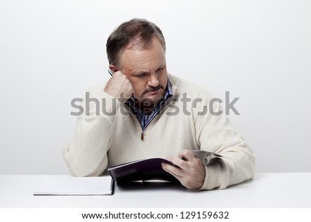 Businessman reading a magazine during office hours over white background