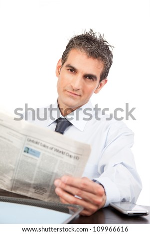 Businessman reading a newspaper at work isolated on white background.