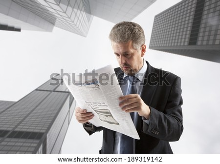 Businessman reading a newspaper, city backgrounds