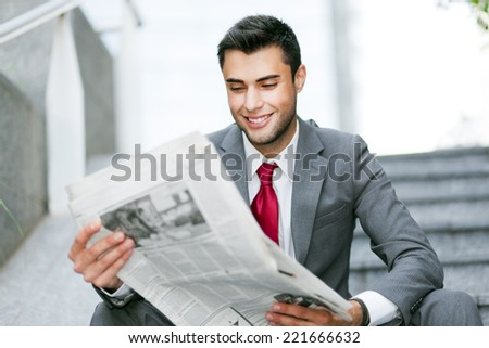 Businessman reading a newspaper in an urban environment  - stock photo