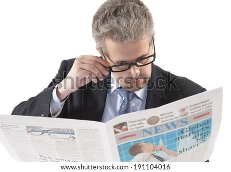 Businessman reading a newspaper on a white background