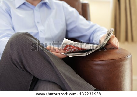 Businessman reading a newspaper whilst relaxing on a sofa