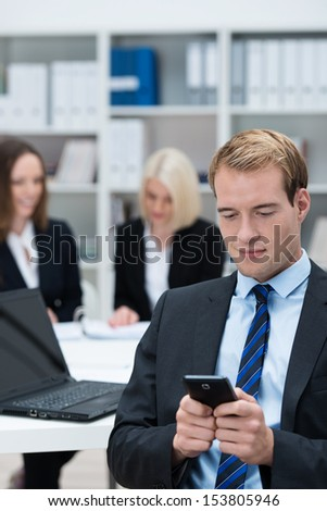 Businessman reading a text message on his mobile phone while sitting in a busy corporate office - stock photo