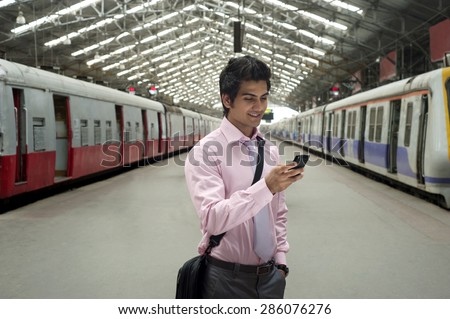 Businessman reading an sms at a train station - stock photo