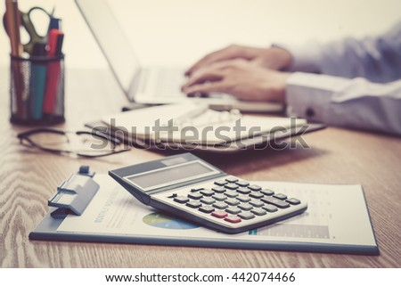 businessman reading document with numbers and calculating - stock photo