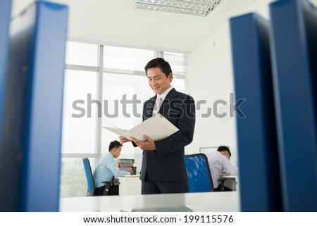 Businessman reading documents in the office - stock photo